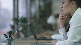 Peinzende vrouwen trommelende vingers op lijst bij laptop, die over nieuw project denken stock footage