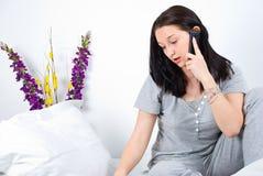 Peinzende vrouwenbespreking bij telefoon op bed Royalty-vrije Stock Afbeeldingen