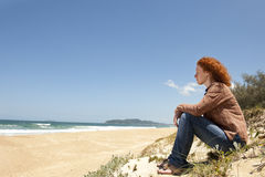 Peinzende vrouwenzitting op de duinen Royalty-vrije Stock Afbeeldingen