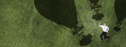 Peinzende zakenman op gras stock afbeeldingen