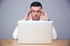 Peinzende zakenmanzitting bij de lijst met laptop Stock Afbeelding