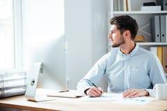 Peinzende zakenmanzitting met laptop op kantoor Stock Afbeeldingen