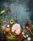 Peito de frango, colher de madeira e ingredientes deliciosos frescos para cozinhar no fundo rústico, vista superior, quadro Imagens de Stock