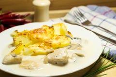Peito de frango com molho de cogumelo e batatas da bronzagem com queijo Imagem de Stock