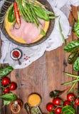 Peito de frango com vegetais e os ingredientes deliciosos para cozinhar no fundo de madeira rústico, vista superior, quadro Imagem de Stock Royalty Free