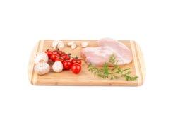 Peito de frango cru com os vegetais na madeira Fotografia de Stock