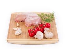 Peito de frango cru com os vegetais na madeira Imagem de Stock