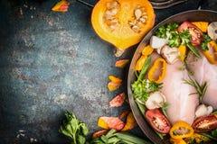 Peito de frango cru em cozinhar o potenciômetro com os ingredientes da abóbora e dos vegetais no fundo rústico escuro Imagens de Stock Royalty Free