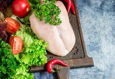Peito de frango cru, vegetais e salada verde na placa de desbastamento Imagem de Stock Royalty Free