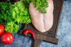 Peito de frango cru, vegetais e salada verde na placa de desbastamento Imagem de Stock