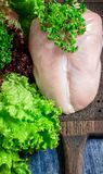 Peito de frango cru, vegetais e salada verde na placa de desbastamento Fotos de Stock Royalty Free