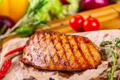 Peito de frango grelhado com especiarias e ervas na placa de madeira imagens de stock