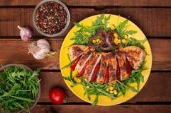 Peito de frango grelhado com salada verde da rúcula e dos vegetais em uma placa amarela Fundo rústico de madeira Vista superior Imagens de Stock