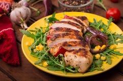 Peito de frango grelhado com salada verde da rúcula e dos vegetais em uma placa amarela Fundo rústico de madeira Vista superior Fotos de Stock