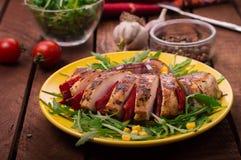 Peito de frango grelhado com salada verde da rúcula e dos vegetais em uma placa amarela Fundo rústico de madeira Vista superior Fotografia de Stock