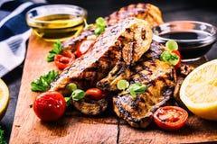 Peito de frango grelhado em variações diferentes com tomates de cereja, cogumelos, ervas, o limão cortado em uma placa de madeira imagem de stock royalty free