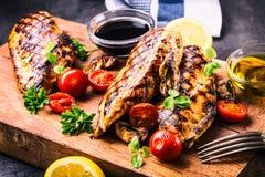 Peito de frango grelhado em variações diferentes com tomates de cereja, cogumelos, ervas, o limão cortado em uma placa de madeira Foto de Stock