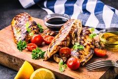 Peito de frango grelhado em variações diferentes com tomates de cereja, cogumelos, ervas, o limão cortado em uma placa de madeira fotografia de stock royalty free
