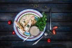 Peito de galinha enchido com espinafre e queijo Em uma placa bonita com os tomates triturados e os verdes das batatas Vista super fotografia de stock