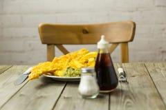 Peixe com batatas fritas britânico em uma placa da cópia do jornal fotografia de stock royalty free