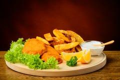 Peixe com batatas fritas em uma placa de madeira Fotos de Stock Royalty Free