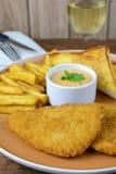 Peixe com batatas fritas esmigalhado com vidro do vinho imagens de stock royalty free