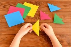 Peixes coloridos do origâmi, folhas de papel, tesouras A criança guarda a folha de papel em suas mãos e fazendo o origâmi pesque foto de stock