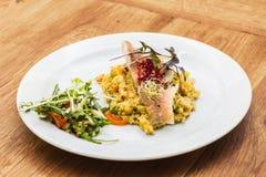 Peixes com os vegetais da mola na placa branca imagem de stock royalty free