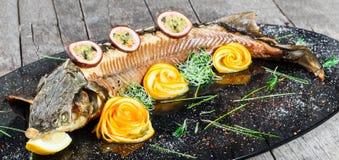 Peixes cozidos do esturjão com alecrins, limão e fruto de paixão na placa no fim de madeira do fundo acima foto de stock