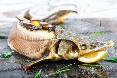 Peixes cozidos do esturjão com alecrins, limão e fruto de paixão na placa no fim de madeira do fundo acima imagem de stock royalty free