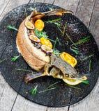 Peixes cozidos do esturjão com alecrins, limão e fruto de paixão na placa no fim de madeira do fundo acima fotos de stock