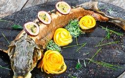 Peixes cozidos do esturjão com alecrins, limão e fruto de paixão na placa no fim de madeira do fundo acima fotografia de stock
