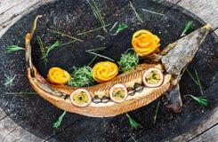 Peixes cozidos do esturjão com alecrins, limão e fruto de paixão na placa no fim de madeira do fundo acima imagens de stock royalty free
