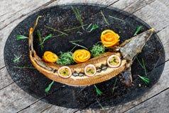 Peixes cozidos do esturjão com alecrins, limão e fruto de paixão na placa no fim de madeira do fundo acima Alimento saudável imagem de stock royalty free