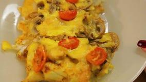Peixes cozidos sob o queijo com cogumelos e tomates de cereja em uma placa branca video estoque