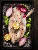 Peixes crus com erva, especiarias e forquilha na bandeja velha preta do revestimento protetor Fotografia de Stock