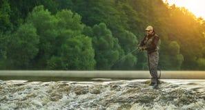 Peixes da caça do pescador do esporte Pesca exterior no rio foto de stock