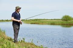 Peixes da pesca de Fisher com haste imagem de stock