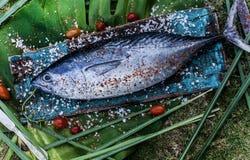 Peixes de atum crus em uma placa de corte com cereja Fotografia de Stock Royalty Free