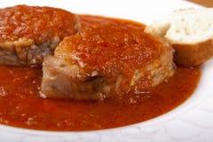 Peixes de atum no molho de tomate e uma fatia de pão. Fotos de Stock