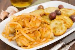 Peixes de bacalhau com cebola e azeite no prato Fotografia de Stock