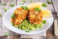 Peixes de bacalhau cozidos nas côdeas de pão ralado com as ervilhas verdes e brócolis triturados foto de stock royalty free