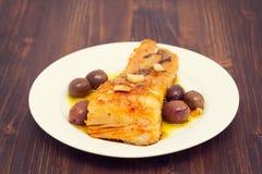 Peixes de bacalhau fritados com alho e azeite no prato Imagem de Stock Royalty Free