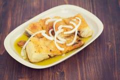 Peixes de bacalhau fritados com cebola e azeite no prato Fotografia de Stock Royalty Free
