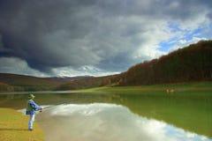 Peixes de travamento do pescador em um lago fotografia de stock