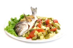 Peixes do sargo com os vegetais na placa branca imagem de stock