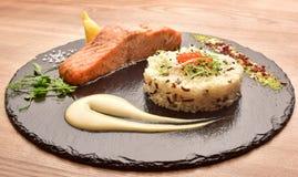 Peixes e arroz em uma bandeja de madeira redonda preta imagem de stock royalty free