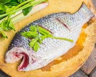 Peixes e especiarias em uma placa de corte de madeira Imagens de Stock Royalty Free