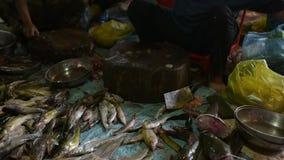 Peixes frescos crus que encontram-se na mesa de madeira no mercado local da cidade de Banlung filme