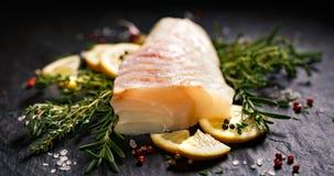 Peixes frescos, faixa de bacalhau crua com adição de ervas e fatias do limão no fundo de pedra preto Imagem de Stock Royalty Free